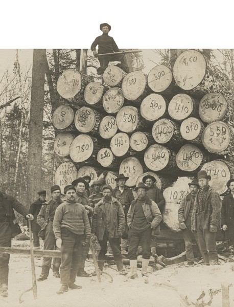 Minnesota lumberjacks standing near a load of numbered logs, 1910. | Photo by Harry F. Nixon, courtesy Minnesota Historical Society