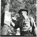 U.S. Forest Service Officer Wilbur Isaacson examines a wild rice season notice posted at Waboose Bay in 1958. For most of the 20th century, tribal members were subject to restrictions on their harvesting of traditional resources, particularly within state and federal lands. | Courtesy of the National Archives and Records Administration, Great Lakes Region, Chicago