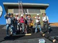 Construction workers from Bois Forte and the Keweenaw Bay Reservation in Michigan share a lighthearted moment while installing a roof on the hotel at the Fortune Bay Casino on the Bois Forte Reservation. | Photo by Helen Wilkie, courtesy of the Bois Forte Band of Chippewa